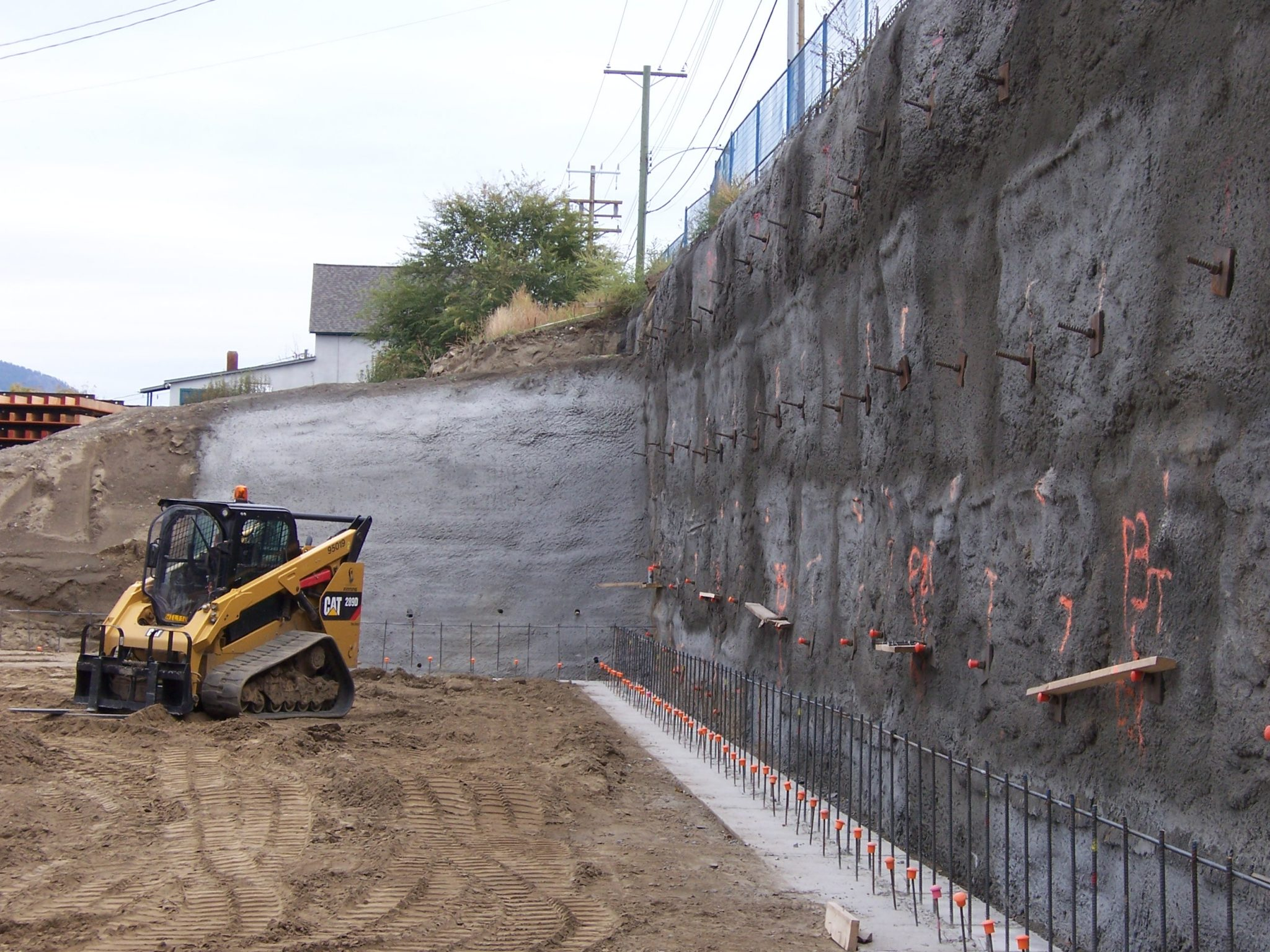 vertical wall with shotcrete and a tracked skid steer